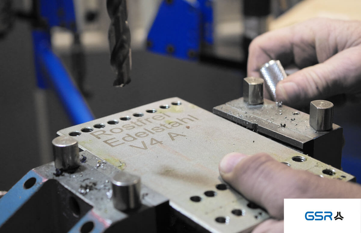 Vorbereitung zum Bohren im Metall: Edelstahlplatte eingespannt im Schraubstock mit Spiralbohrer