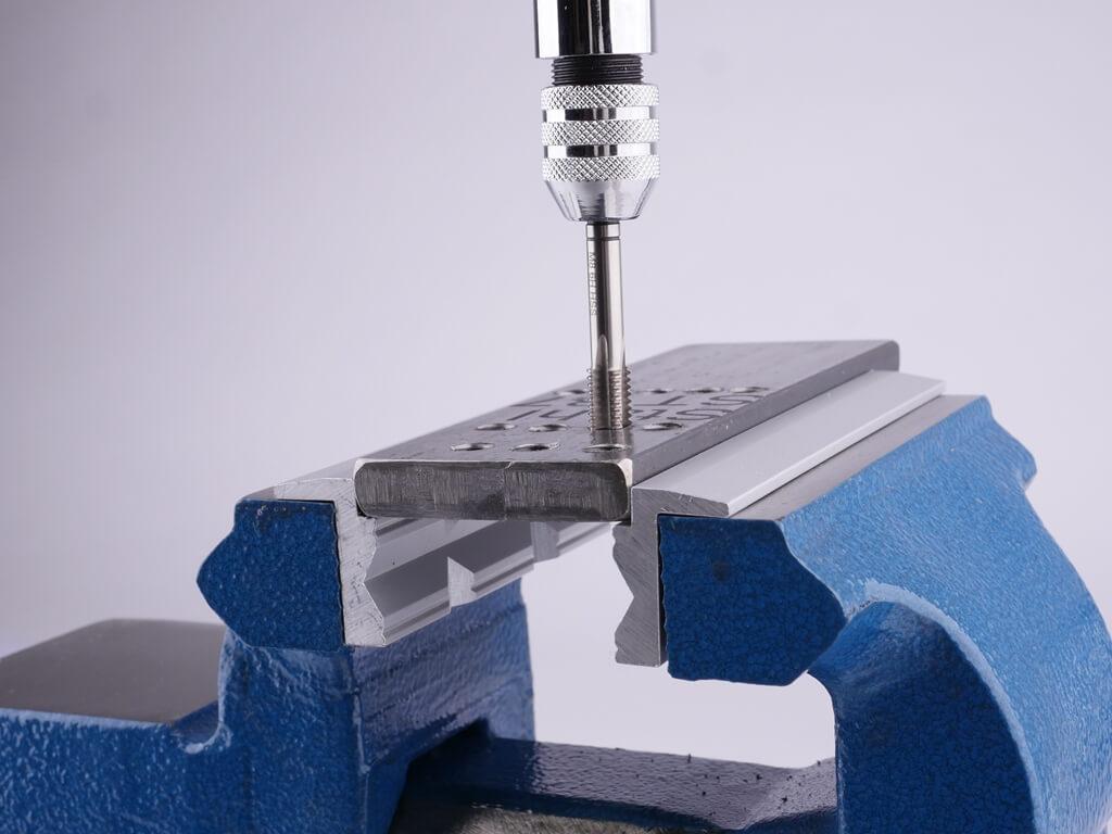 Schonbacken aus Aluminium mit Prismenprofil eingespannt im Schraubstock. In das eingespannte Werkstück wird mit einem Gewindeschneider ein Innengewinde gebohrt