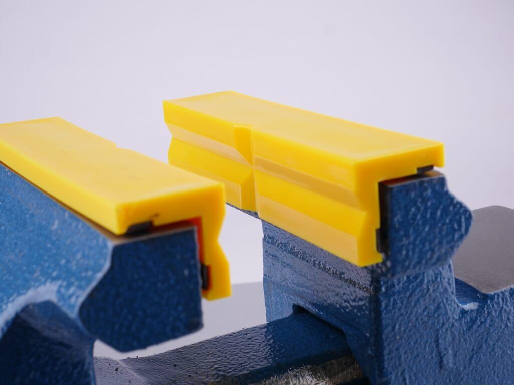 gelbe Kunstoffbacken mit Prismen-Profil eingespannt im Schraubstock
